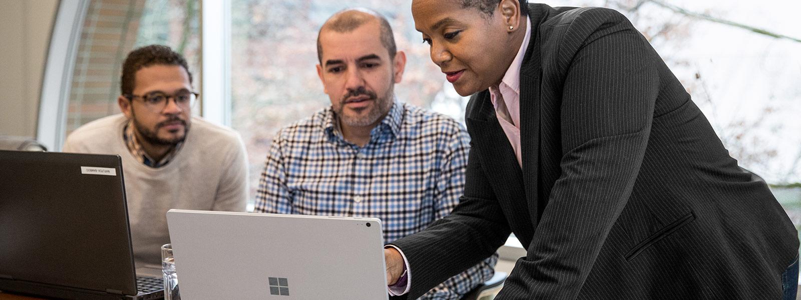 Tre persone che interagiscono con portatili in un ambiente d'ufficio