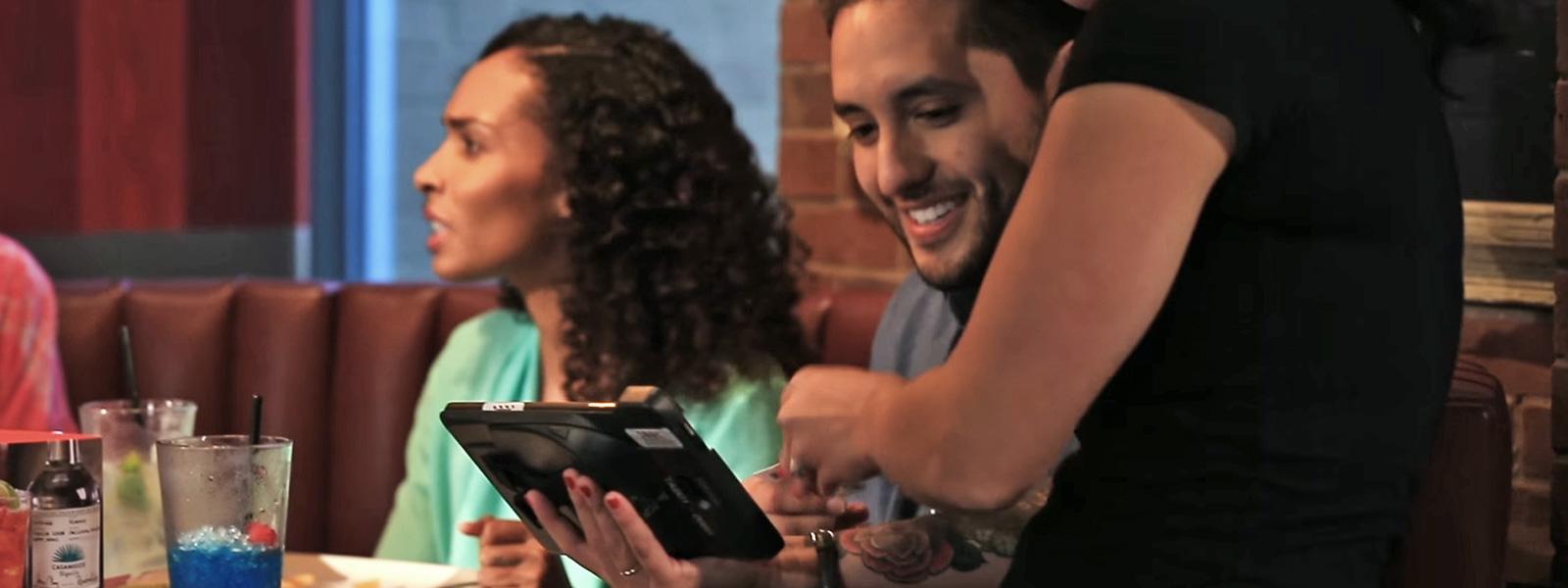 Clienti di TGI Fridays che interagiscono con il dispositivo al tavolo