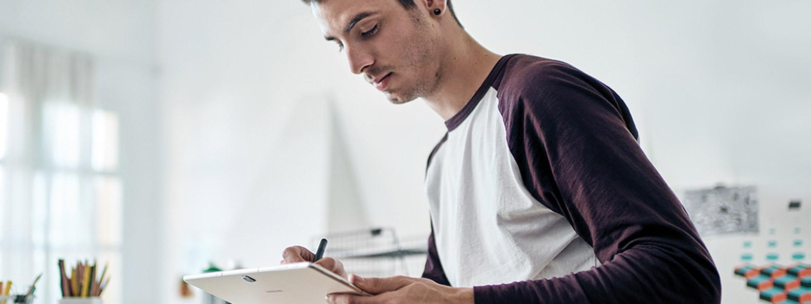 Uomo seduto alla scrivania che usa Samsung Galaxy TabPro S