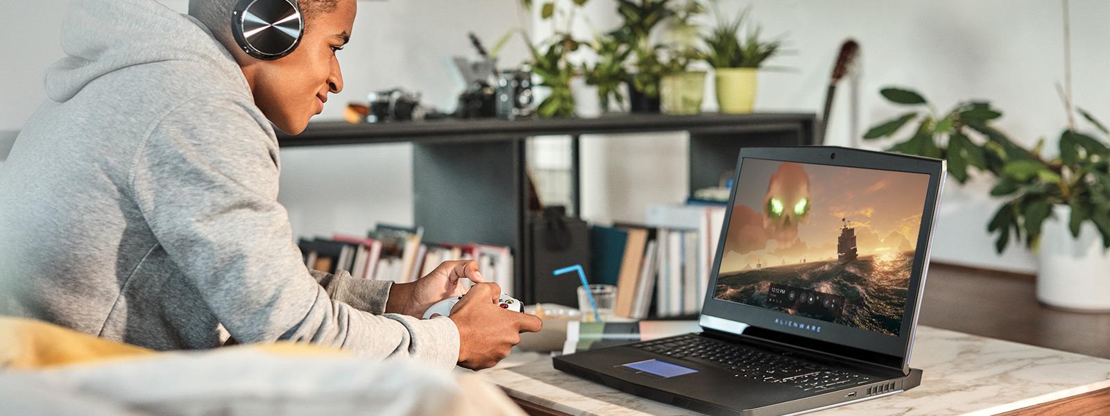 Un uomo con le cuffie usa un controller Xbox per giocare con Sea of Thieves su un portatile di gioco Windows 10