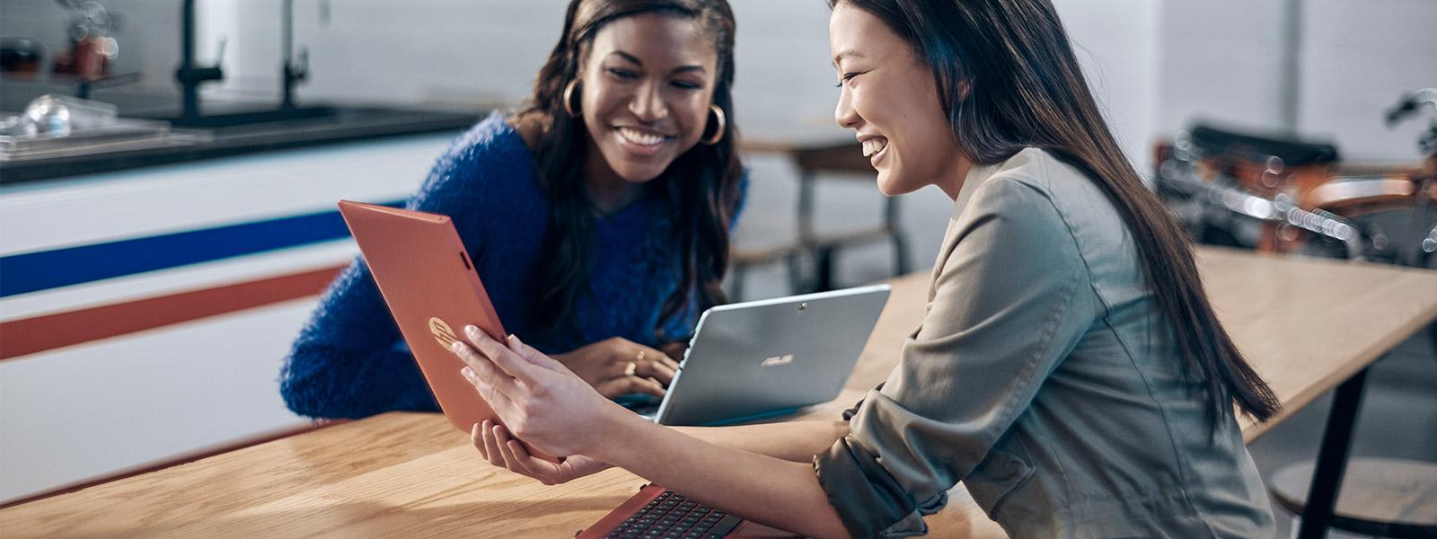 Due donne sedute a un tavolo osservano lo schermo di un tablet sostenuto fra loro da un'altra donna