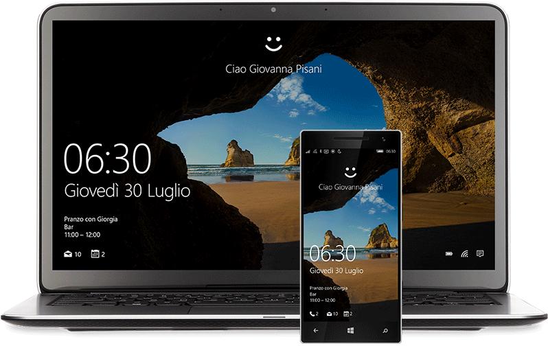 """Laptop e telefono con la schermata Start di Windows10. C'è una faccia sorridente sopra le parole di """"Hello Miranda Vance"""""""