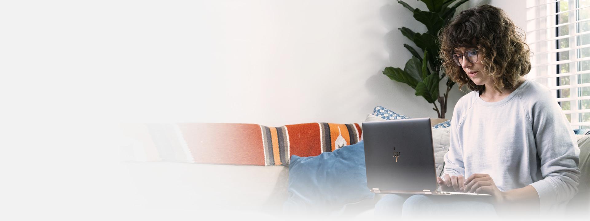ソファに座ってノート PC を使っている女性