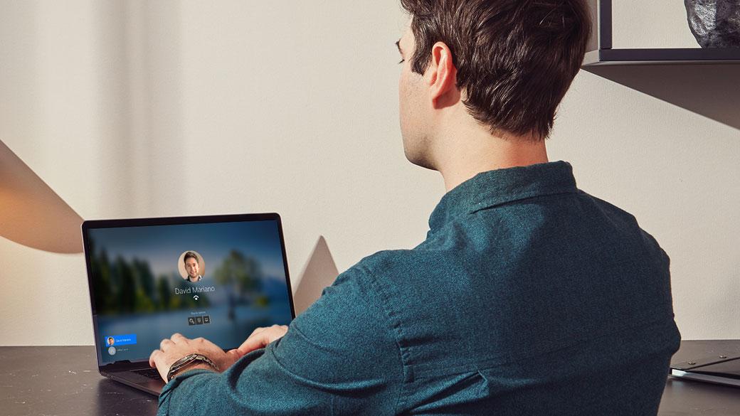 デスクに座っている男性が Windows Hello でラップトップにサインインする