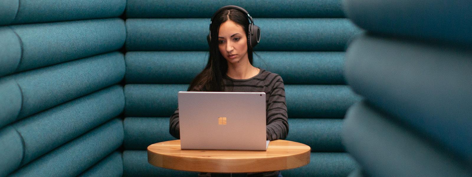 女性は Windows 10 コンピューターで作業しながら、ヘッドフォンを着用し、静かに座っています