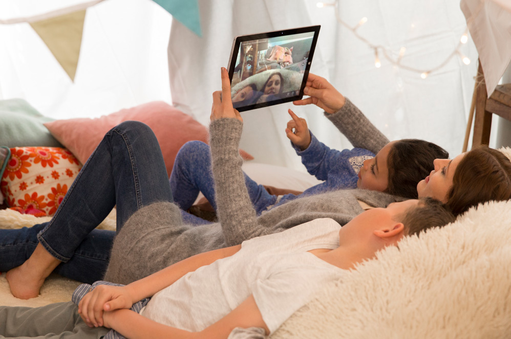 Windows 10 搭載のコンピューターで写真を見ながらソファーでくつろいでいる子供