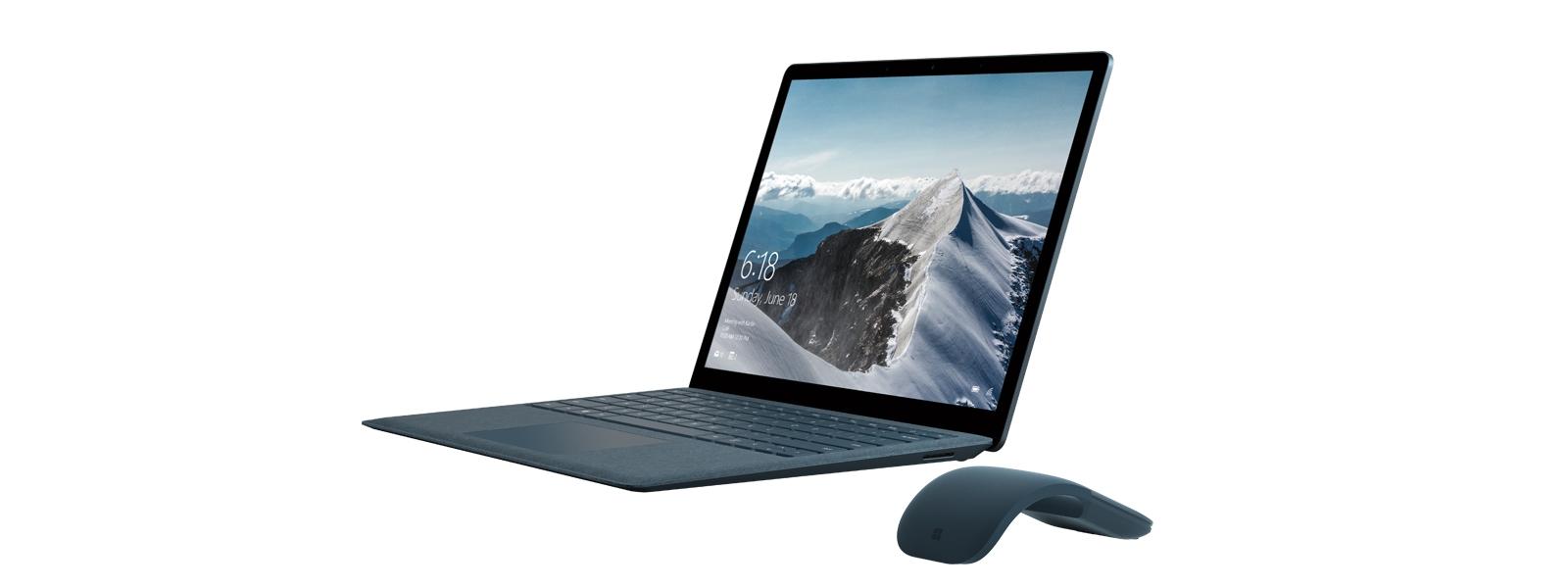 コバルト ブルーのアーク タッチ マウスが横に置かれた、雪山の背景画面が表示されたコバルト ブルーの Surface Laptop を斜めから見た図。