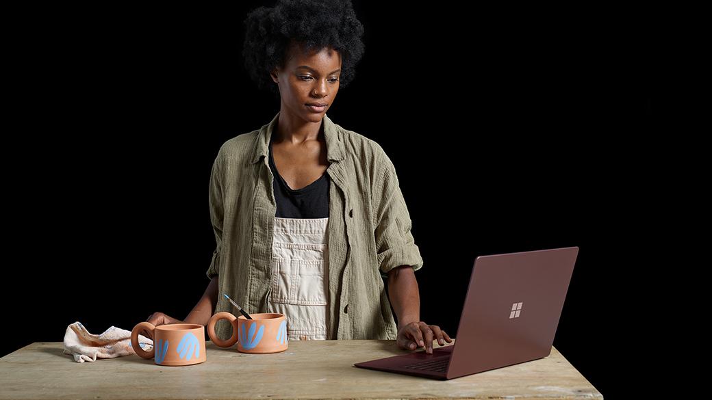 Surface Laptop とセラミックカップ製品と共に写る Kenesha さん。