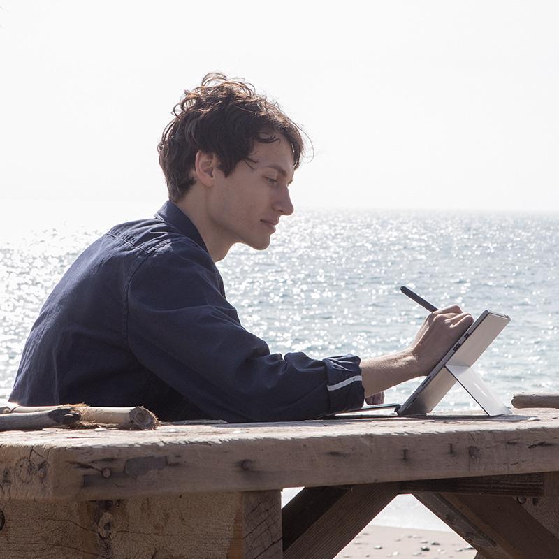 Edsta さんは外で Surface ペンを使い Surface Pro で作業しています。