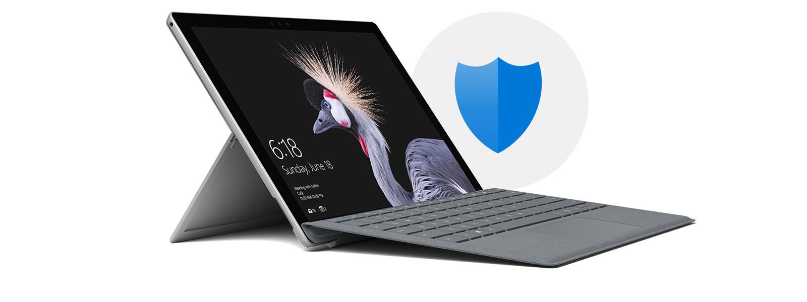 セキュリティ保護アイコンが背景にある、スタート画面が表示され、右向きで置かれているラップトップモードの Surface Pro。