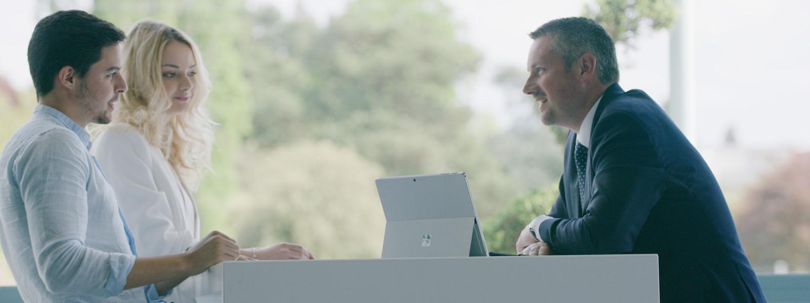 Surface Pro が置かれているデスクに腰掛ける 3 名の背景に野外のセットがある様子。