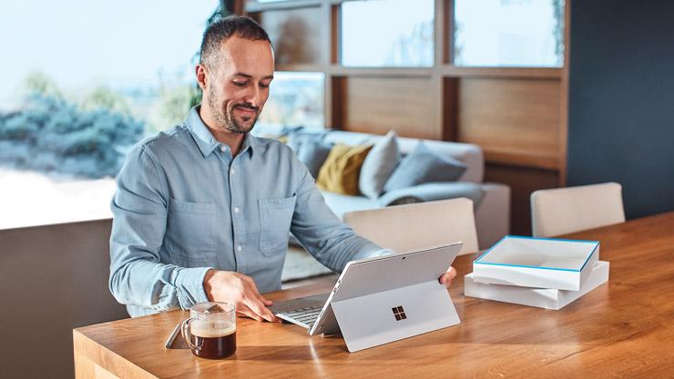 職場にあるテント モードの Surface デバイスと机に座っている男性
