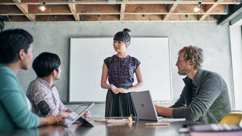 会議室でプレゼンテーションを行う女性。