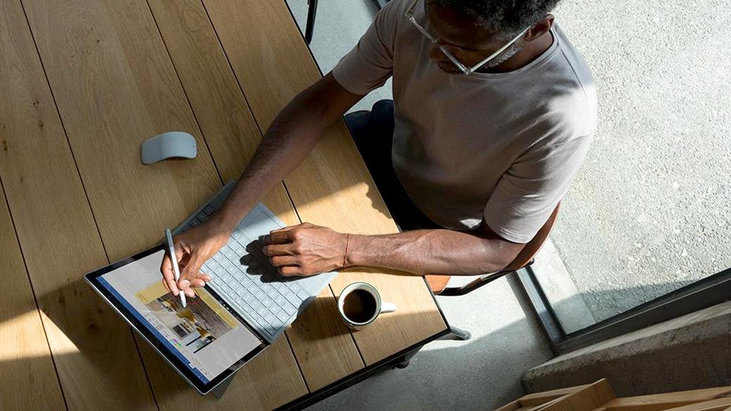 机に座り Surface Laptop で Arc Mouse と Surface ペンを使っている男性