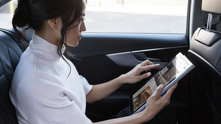 車の中で移動中にタブレット モードの Surface デバイスを使う女性