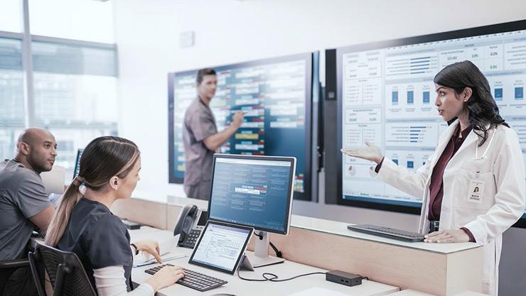 教室に座り、テント モードの Surface デバイスと Surface Hub を使って共同作業する 3 人