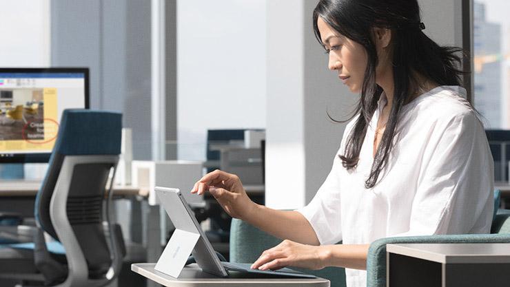 オープンなオフィスのホットデスクでSurface Proで作業する女性