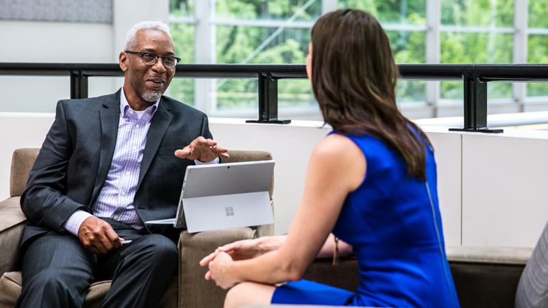 Surface Proを使用する男性が目の前の女性と意見を交換