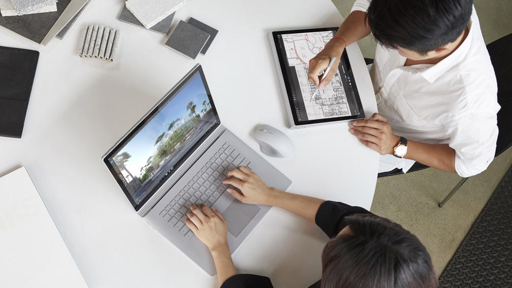 1 人はラップトップ モード、もう 1 人はタブレット モードの Surface Book で作業をしている 2 人