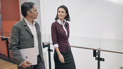 男性が Surface Book を右手で持ち、職場で女性と並んで歩く。