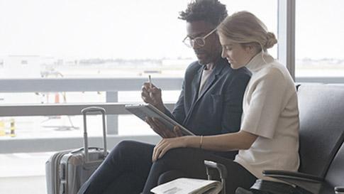 空港で移動しながら Surface デバイスを操作している 2 名の男性。