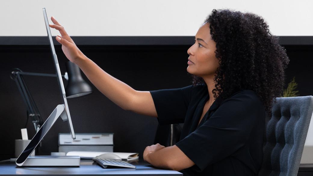 Surface Studio 2のディスプレイ上のインターフェースに触れる女性