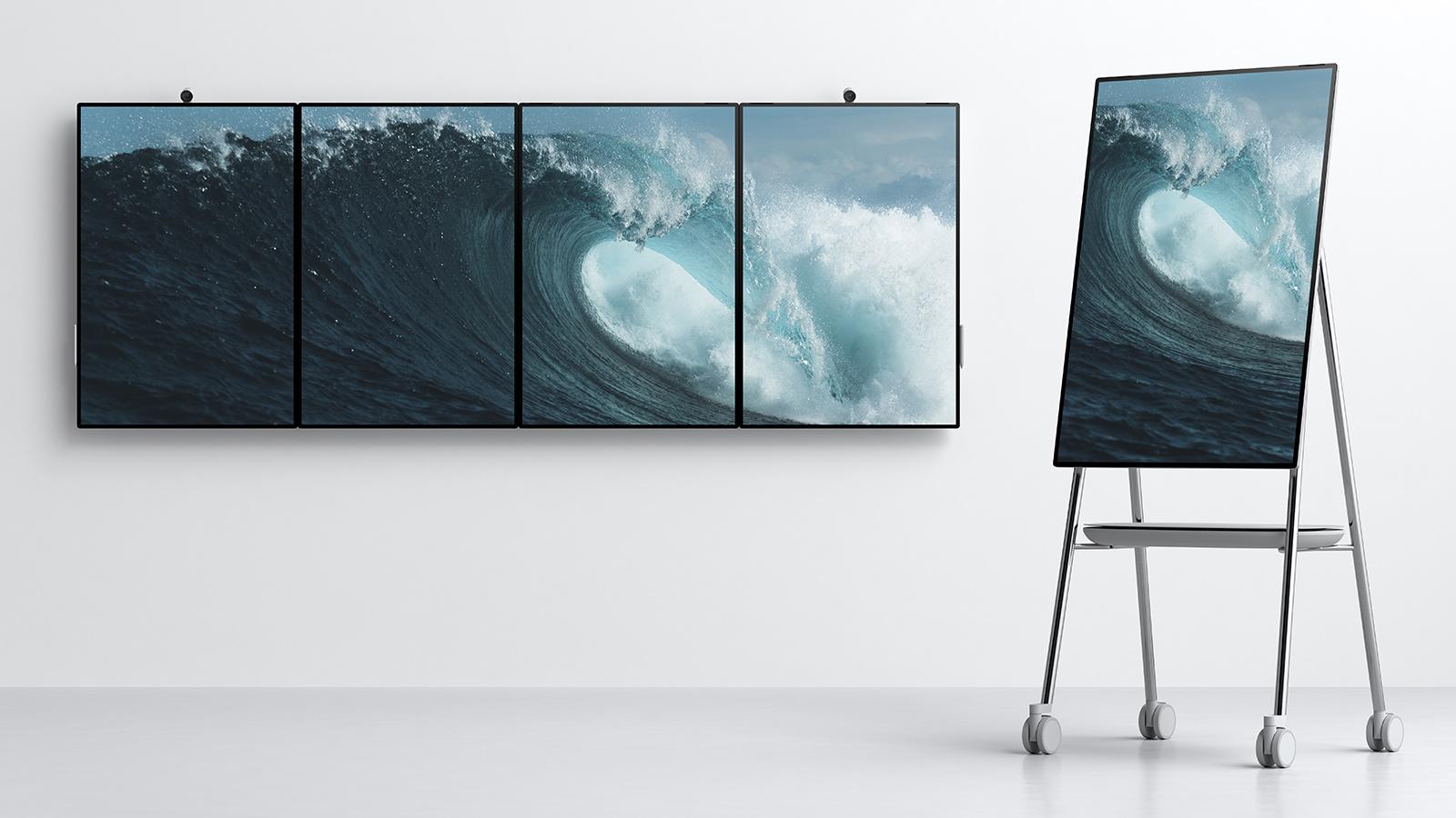 壁にタイル状につなげられた横向きの Surface Hub 2 が 4 台と、 Steelcase によるデザインのスタンドに載せられて縦向きに回転された Surface Hub 2 が 1 台