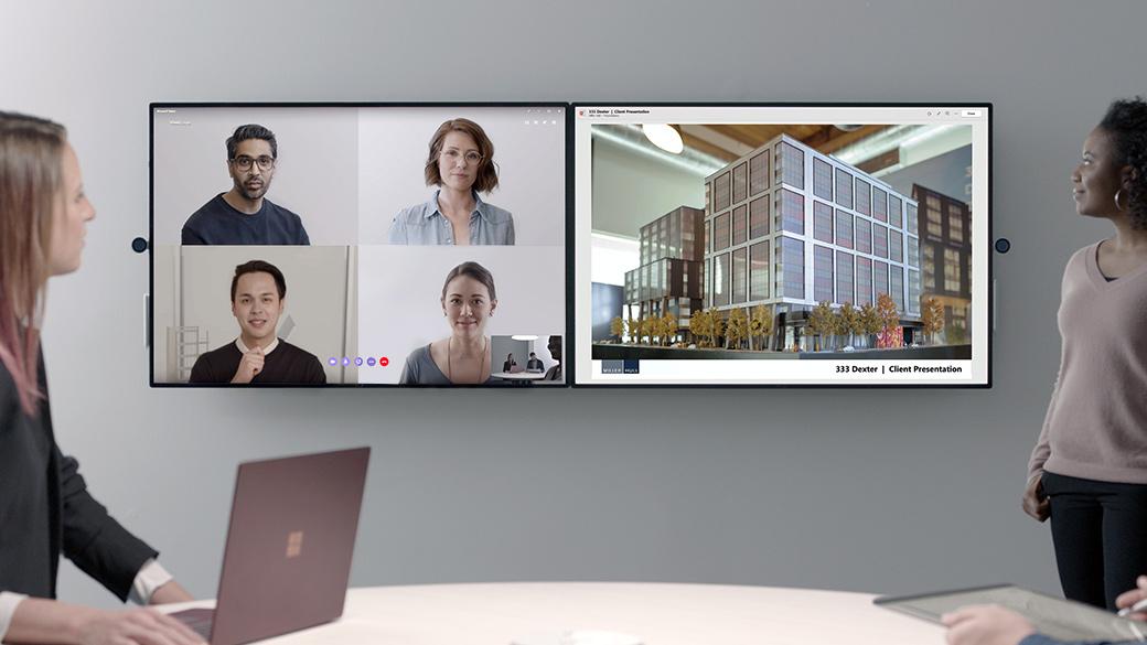 チームのスペースで二人の女性が Surface Laptop で作業をし、横向きでタイル状につなげられた 2 台の Surface Hub 2 上の 4 人とビデオ会議で打ち合わせをしている。