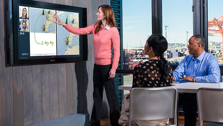 会議室で Surface Hub を使ってプレゼンテーションをしている女性。