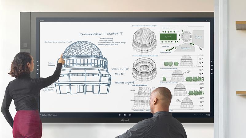 Surface Hub を使って男性にプレゼンをしている女性。
