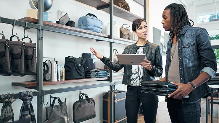 Surface Pro 4 を使用して服屋でお客様にデモンストレーションを行う女性