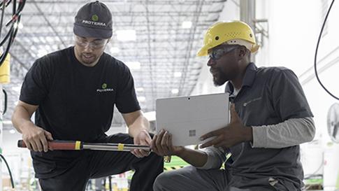 Surface Pro で作業を行っている 2 名のエンジニア。