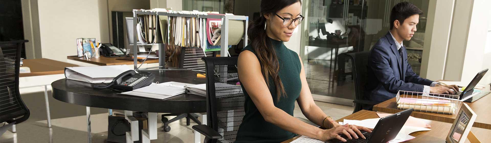 オフィスでデスクを囲んで、Office 365 を表示したノート PC を使用している 2 人の人物。