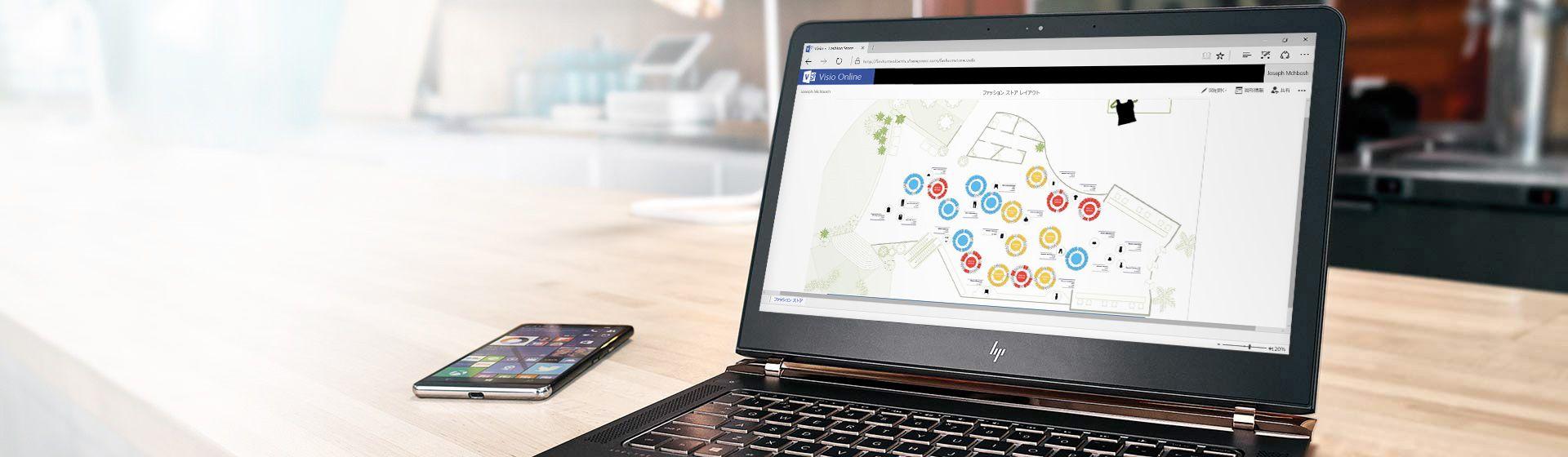 テーブルの上にスマートフォンがあり、その横のノート PC の画面に Visio Online の図面が表示されています