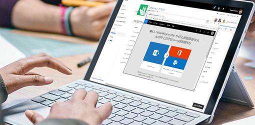 Flow と SharePoint が実行されているノート PC でキーボードを打っている手