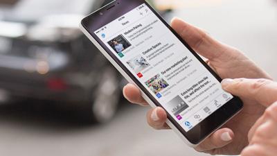 手に持ったスマートフォンで実行中の SharePoint