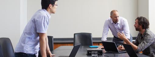 ノート PC が置かれた会議テーブルを囲んで会議をしている 3 人の男性