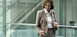 電話を見ながら、Exchange Online Archiving の機能と価格について確認する女性。
