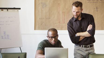 2 人の男性が 1 台のノート PC の画面を見て Office 365 を使用しています