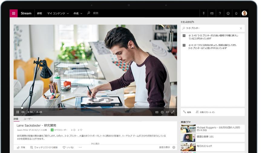 オフィスの机で仕事をしている人の Stream ビデオを再生中のデバイス。右側はビデオのトランスクリプト