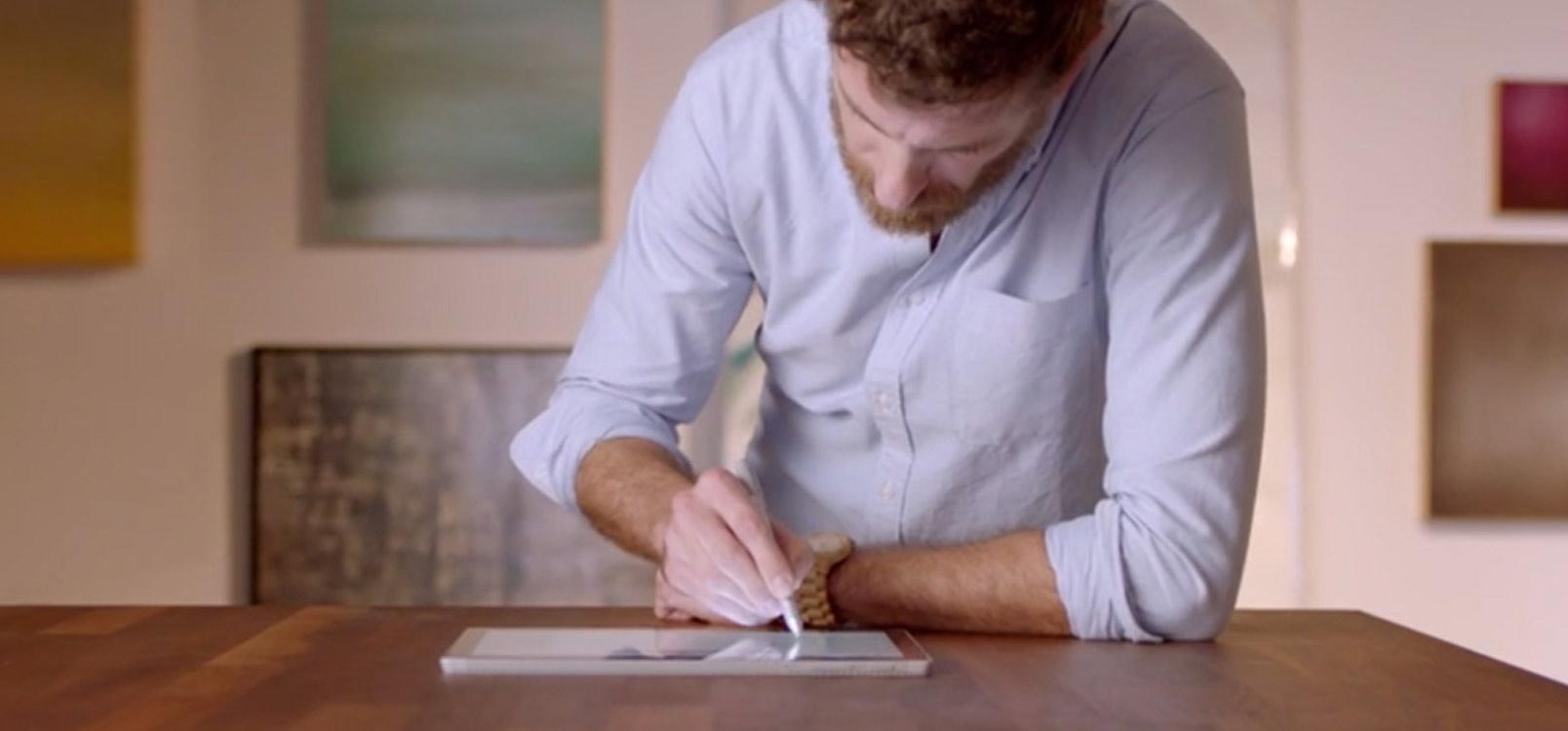 2 人の人物がスマートフォンの画面を見ています。Office での共同作業に関する詳細情報を参照します。