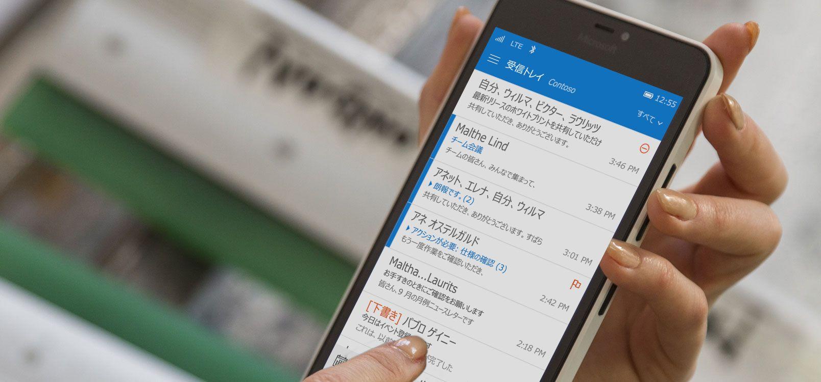 スマートフォンで Office 365 のメール リストのメッセージをタップしています。