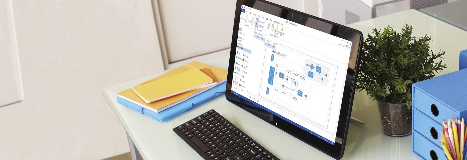 机の上のタブレット コンピューターに Visio Professional 2016 のプロセス図が表示されている