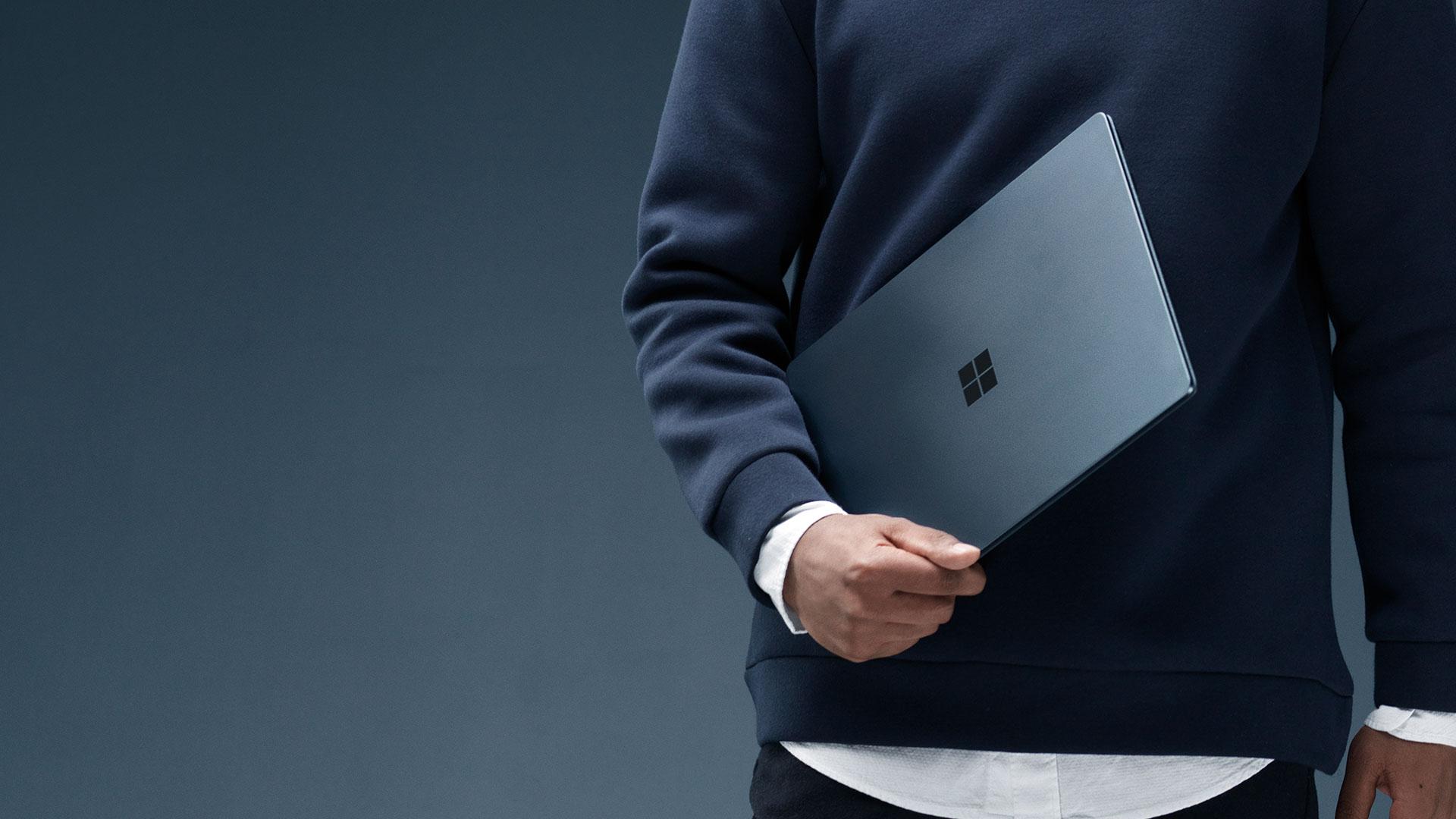 コバルト ブルーの Surface Laptop を持っている男性