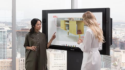 二人の女性が Surface Hub でタッチスクリーンを使い、 Microsoft Whiteboard アプリでデザイン上に絵を描いている。