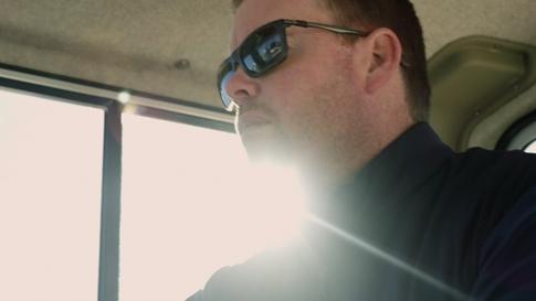 Bay Equity の Brett McGovern が天気のいい日に車を運転している。