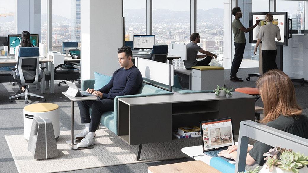 現代的な職場で同僚たちが様々な Surface デバイスを使っている。 Surface Pro で入力する男性、Surface Laptop で入力する女性、Surface Hub を使っている男女。