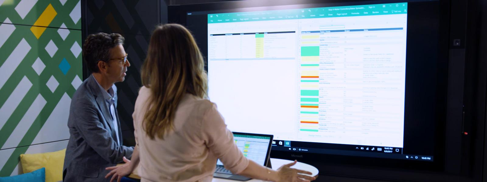 Surface デバイスとうまく働くように設計された 5 箇所の Steelcase のスペースのうちの一つで、女性と男性が Surface Hub を使っている。