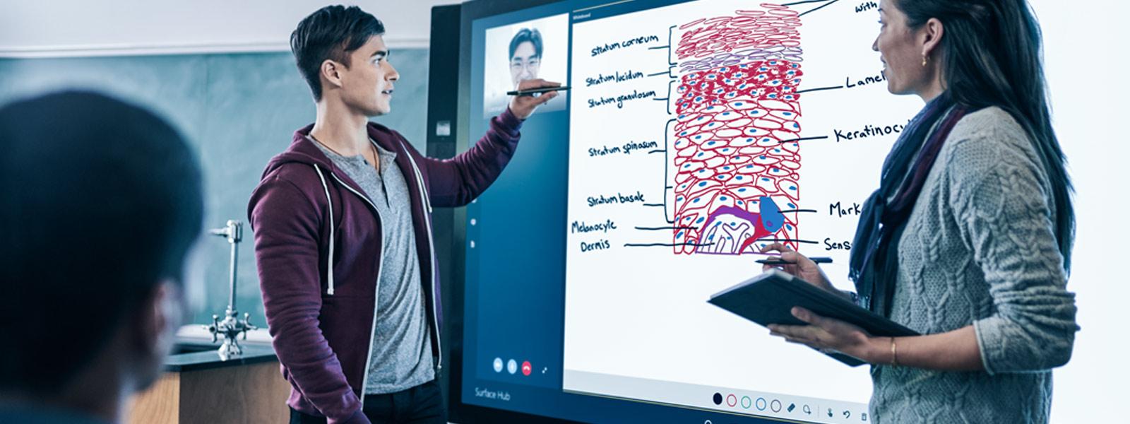 教室で 2 人の生徒が Surface Hub の画面上で Surface ペンを使って Skype と Microsoft Whiteboard を操作している。