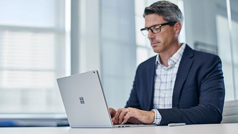Surface Laptop で 作業している男性。